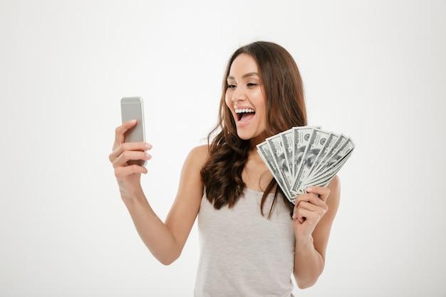 Portret van gelukkige joyous vrouwelijke jaren '30 die veel munt van de gelddollar aantonen terwijl het gebruiken van haar mobiele telefoon, die over wit wordt geïsoleerd Gratis Foto