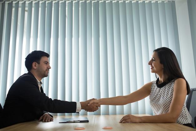 Portret van gelukkige mannelijke en vrouwelijke partners handen schudden Gratis Foto