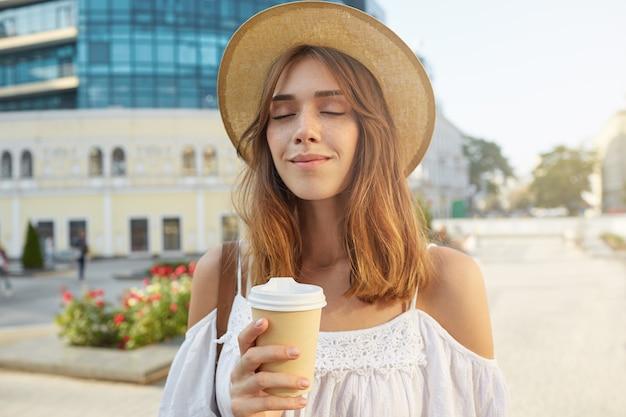 Portret van gelukkige mooie jonge vrouw met gesloten ogen draagt Gratis Foto