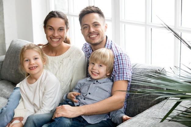 Portret van gelukkige multi-etnische familie die goedgekeurde jonge geitjes omhelst die samen plakken Gratis Foto