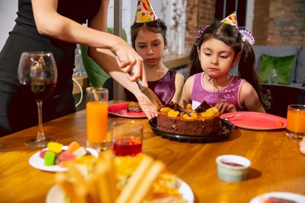 Portret van gelukkige multi-etnische familie die thuis een verjaardag viert. grote familie die cake eet en wijn drinkt terwijl ze groet en leuke kinderen heeft. viering, familie, feest, thuisconcept. Gratis Foto