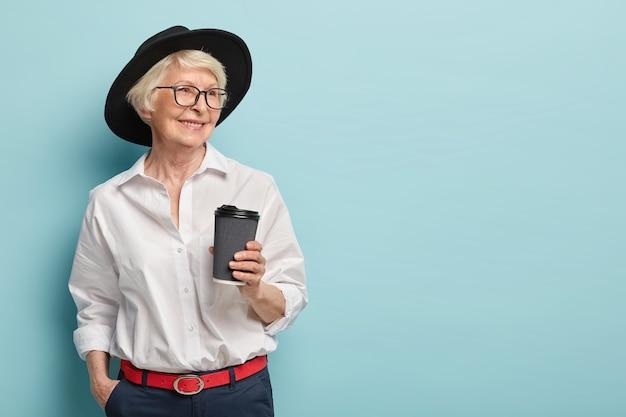 Portret van gelukkige oudere vrouw met pensioen, heeft een ontmoeting met voormalige collega's, houdt afhaalkoffie, draagt stijlvol wit overhemd, broek met rode riem, houdt hand in zak. vrije tijd, pensioen Gratis Foto