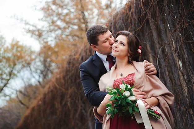 Portret van gelukkige pasgetrouwden in de herfst de natuur. gelukkige en bruid en bruidegom die omhelzen kussen Premium Foto