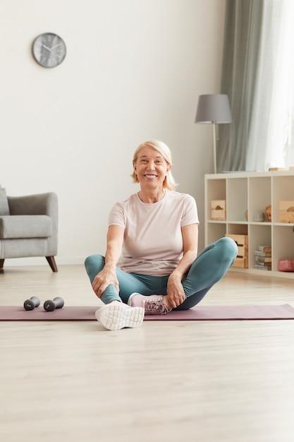 Portret van gelukkige rijpe vrouw zittend op de vloer en rust na sporttraining thuis ze lachend Premium Foto