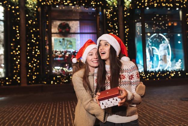 Portret van gelukkige schattige jonge vrienden elkaar knuffelen en glimlachen tijdens het wandelen op kerstavond buitenshuis. Gratis Foto