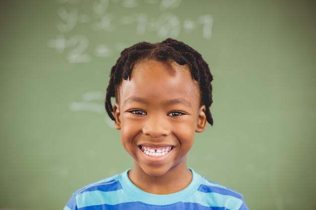 Portret van gelukkige schooljongen die in klaslokaal glimlachen Premium Foto
