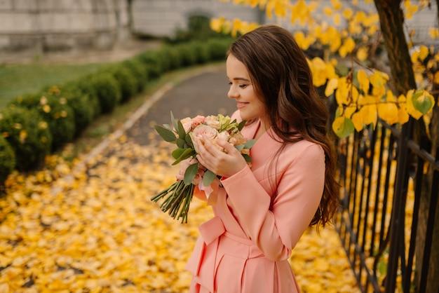 Portret van gelukkige sensuele jonge donkerbruine bruid in roze huwelijkskleding en status in de herfstpark dichtbij uitstekende kathedraal en het houden van huwelijksboeket. Premium Foto