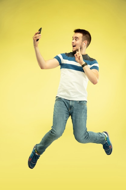 Portret van gelukkige springende man met gadgets op gele muur Gratis Foto