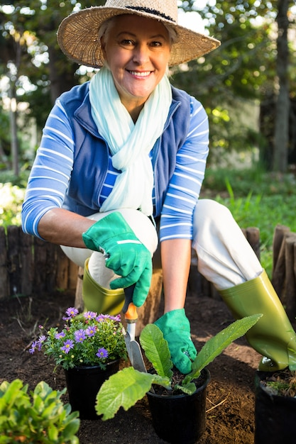 Portret van gelukkige tuinman die bij tuin plant Premium Foto