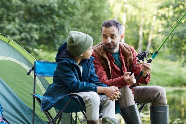 Portret van gelukkige vader praten met zoontje terwijl u geniet van visreis samen en kamperen in de natuur Premium Foto