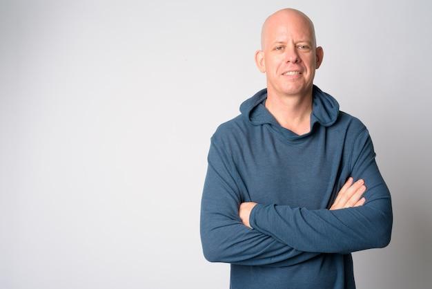 Portret van gelukkige volwassen knappe kale man die lacht met gekruiste armen Premium Foto