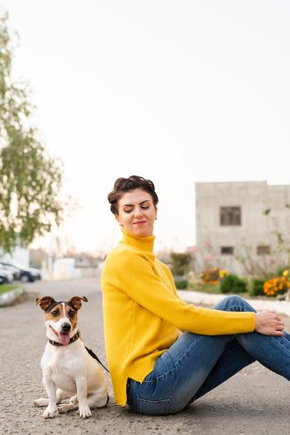 Portret van gelukkige vrouw met haar hond in openlucht Gratis Foto