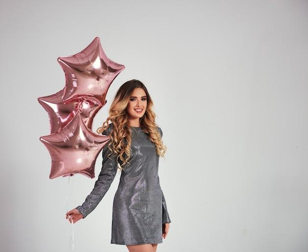 Portret van gelukkige vrouw met stervormige ballonnen Gratis Foto