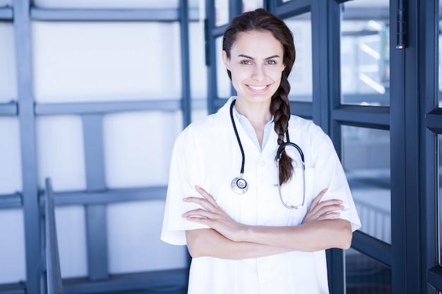 Portret van gelukkige vrouwelijke arts die zich met die wapens bevinden in het ziekenhuis worden gekruist Premium Foto