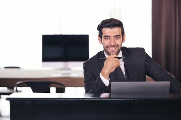 Portret van gelukkige zakenman achter bureau Premium Foto