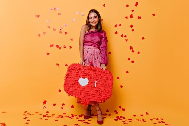 Portret van gemiddelde lengte van aantrekkelijk meisje dat zich op sinaasappel met confettien bevindt. betoverende vrouw in roze jurk met plezier. Gratis Foto