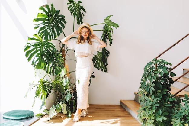 Portret van gemiddelde lengte van dromerig meisje in witte sneakers en rok staan met handen omhoog in de schaduw van grote groene bloem Gratis Foto