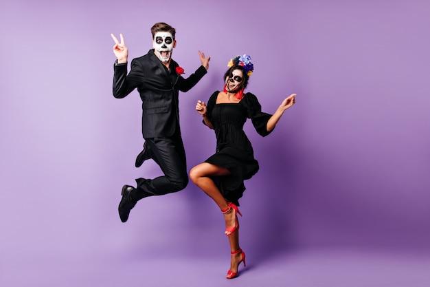 Portret van gemiddelde lengte van europees paar dat op purpere achtergrond in zombiekostuums danst. grappige jonge mensen gek rond op halloween-evenement. Gratis Foto