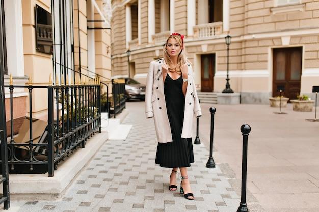 Portret van gemiddelde lengte van mooie vrouw in vintage kleding die zich met gekruiste benen voor mooie gebouwen bevindt. buiten foto van glamoureuze blond meisje lichtbruine jas en trendy schoenen dragen. Gratis Foto