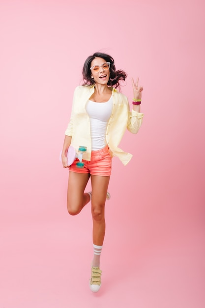 Portret van gemiddelde lengte van schattige spaanse jonge dame in roze korte broek springen met een glimlach. zalig skatermeisje in sportieve schoenen die pret hebben. Gratis Foto