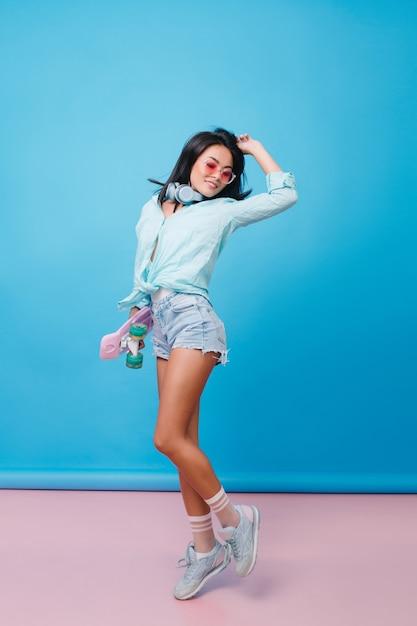 Portret van gemiddelde lengte van slanke spaanse vrouw die gelukkige emoties uitdrukt. sensueel latijns meisje met gebruinde huid in straatoutfit dansen met hand omhoog. Gratis Foto