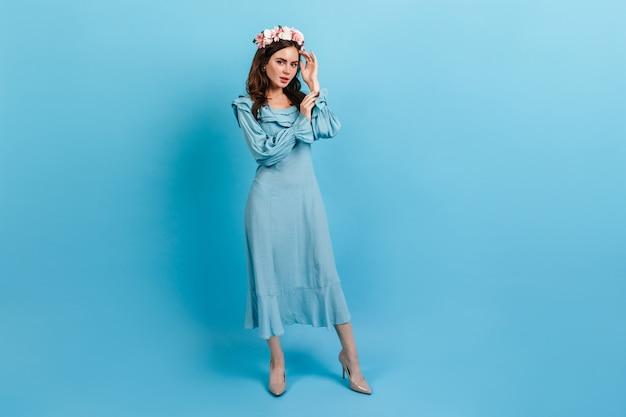 Portret van gemiddelde lengte van verfijnde dame in midi-jurk. vrouw met kroon van bloemen op blauwe muur. Gratis Foto