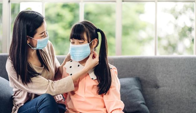Portret van geniet van gelukkige liefde aziatische moeder die beschermend masker draagt voor klein aziatisch meisjeskind in quarantaine voor coronavirus met sociale afstand thuis Premium Foto