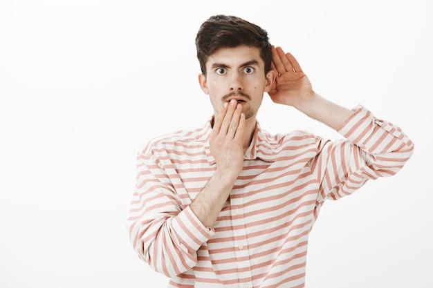 Portret van geschokt geïntrigeerde aantrekkelijke blanke man in trendy gestreept shirt, hand in de buurt van oor en mond, gesprek afluisteren of afluisteren, iets schokkends en interessants horen Gratis Foto