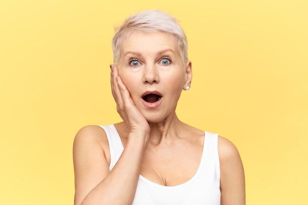 Portret van geschokt volwassen europese vrouw die naar adem snakt met geopende mond, verrast, hand op de wang houdt, iets belangrijks vergeten, verward gefrustreerde gezichtsuitdrukking Gratis Foto