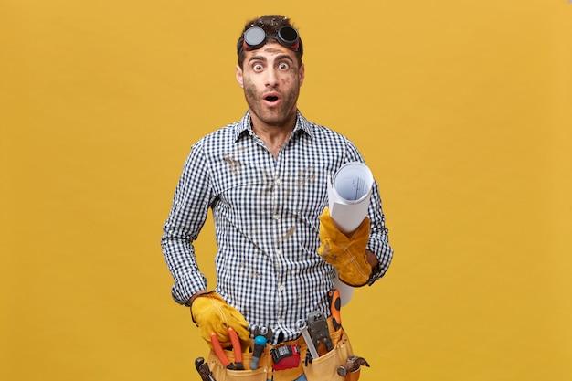 Portret van geschokte klusjesman met geruit overhemd, beschermende brillen en handschoenen, gereedschapsriem met opgerold papier met verbaasde uitdrukking die zijn fout realiseert. mensen en werkconcept Gratis Foto