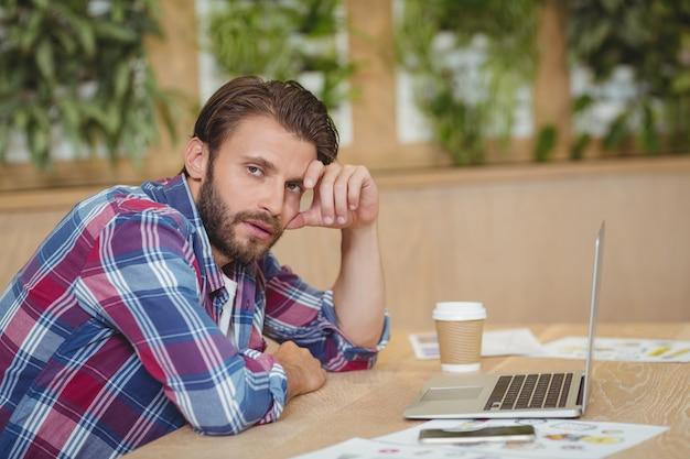 Portret van gespannen directeur met laptop die bij bureau situeert Premium Foto