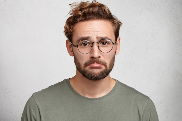 Portret van gestrest gefrustreerde man kromt onderlip wordt misbruikt door iemand, heeft woedeaanval Gratis Foto