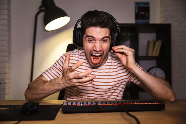 Portret van gestrest jongeman 20s met hoofdtelefoon schreeuwen, zittend aan een bureau in de kamer en het spelen van videogames Premium Foto