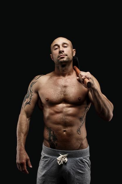 Portret van getatoeëerde shirtless atleet met hamer op schouder Premium Foto