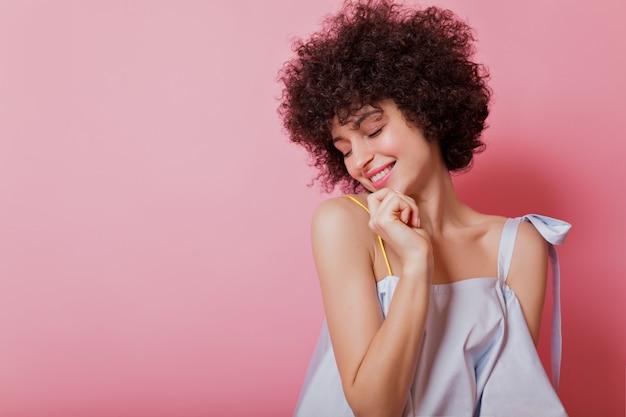 Portret van gevoelige kortharige met ringetjes vrouw gekleed hemelsblauwe blouse vormt met charmante glimlach op roze Gratis Foto