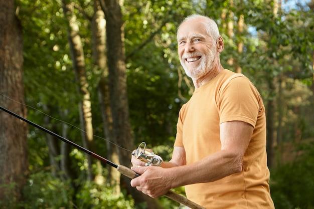Portret van gezonde glimlachende bebaarde blanke mannelijke gepensioneerde m / v in t-shirt poseren buitenshuis met groene bomen met hengel, genieten van vissen. recreatie, vrije tijd en natuurconcept Gratis Foto