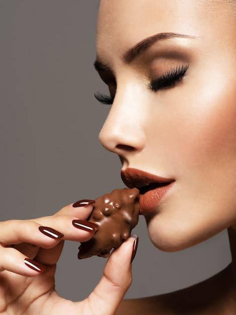 Portret van glamour mooie vrouw houdt en eet chocoladesuikergoed. Gratis Foto