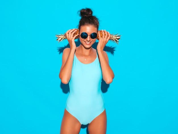 Portret van glimlachend donkerbruin meisje in de zomer badmode badpak en zonnebril. sexy vrouw met verse kleine ananas. positief model poseren in de buurt van blauwe muur. houd het in de buurt van oren Gratis Foto