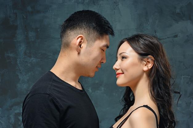 Portret van glimlachend koreaans paar op een grijze muur Gratis Foto