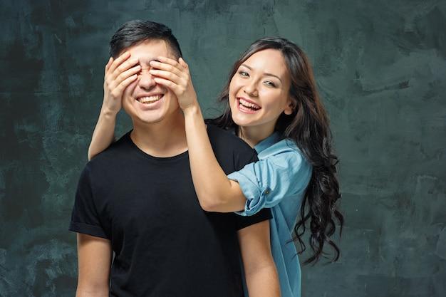Portret van glimlachend koreaans paar op een grijze studio Gratis Foto