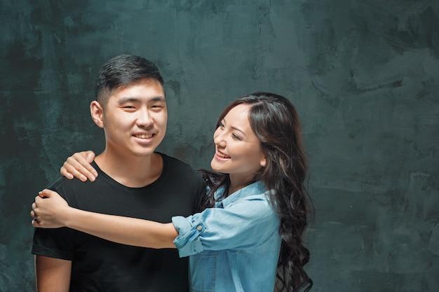 Portret van glimlachend koreaans paar op een grijze studioachtergrond Gratis Foto