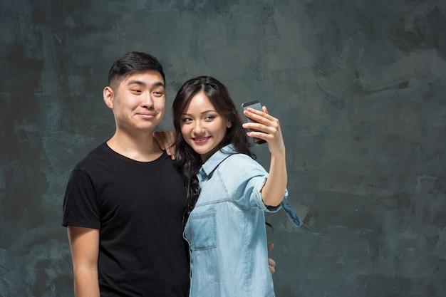 Portret van glimlachend koreaans paar op grijs Gratis Foto