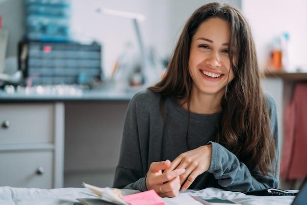 Portret van glimlachend leuk hipstermeisje met het schrijven van universiteitsoefeningen in notitieboekje. Gratis Foto