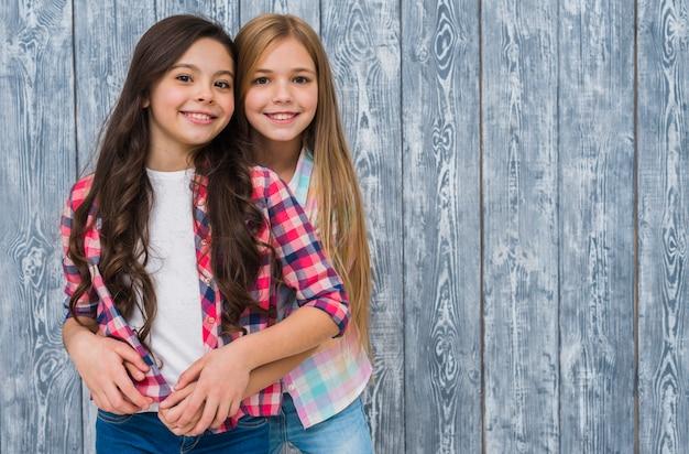 Portret van glimlachend twee mooie meisjes die zich tegen grijze houten textuurmuur bevinden Gratis Foto
