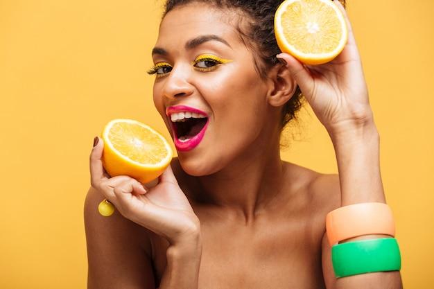 Portret van glimlachende afro amerikaanse vrouw met modieuze make-up die sappige rijpe oranje holdingsdelen in beide handen proeven die dichtbij gezicht, over gele muur worden geïsoleerd Gratis Foto