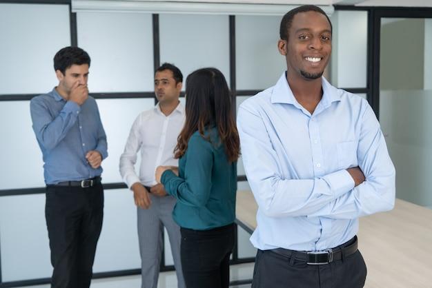 Portret van glimlachende afro-amerikaanse zakenman met armen gevouwen in vergaderruimte. Gratis Foto