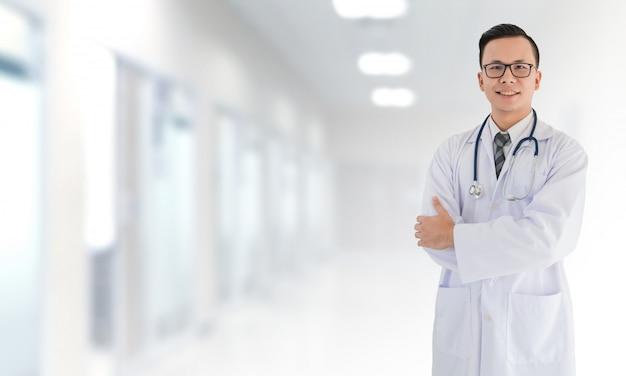 Portret van glimlachende aziatische medische mannelijke arts die zich voor het vage binnenlandse ziekenhuis bevindt Premium Foto