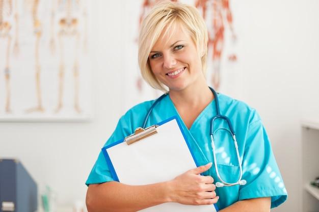 Portret van glimlachende blonde vrouwelijke chirurg Gratis Foto