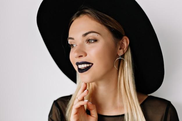 Portret van glimlachende charmante vrouw met zwarte lippenstift en zwarte hoed Gratis Foto