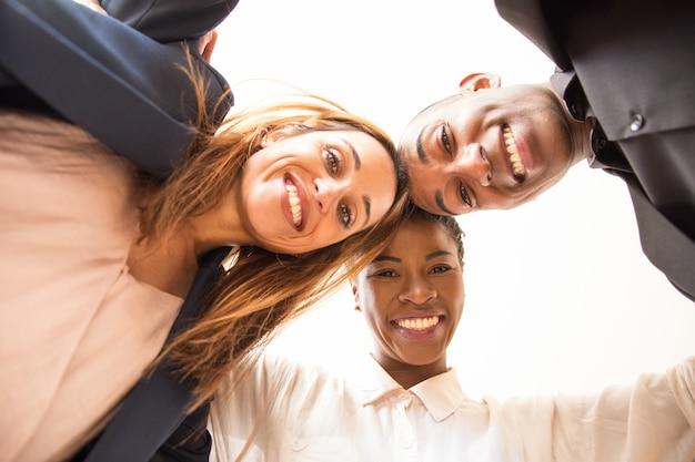 Portret van glimlachende collega's die en camera omhelzen bekijken Gratis Foto